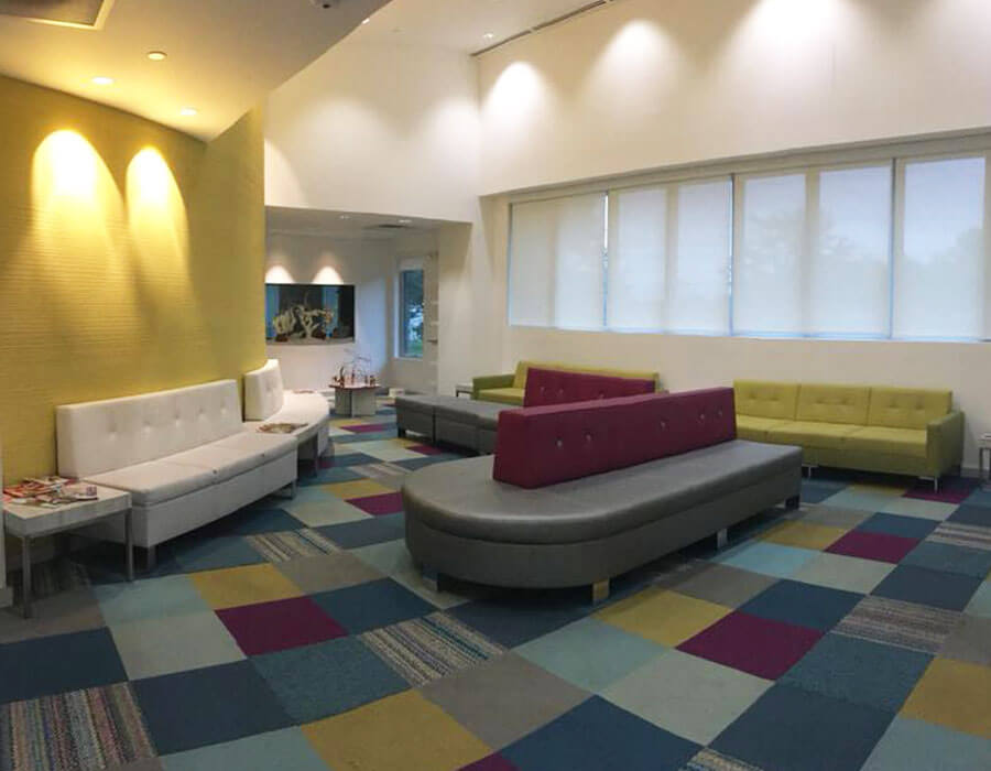 waiting room with grey, green and tan seating, multi-colored carpeting and yellow walls