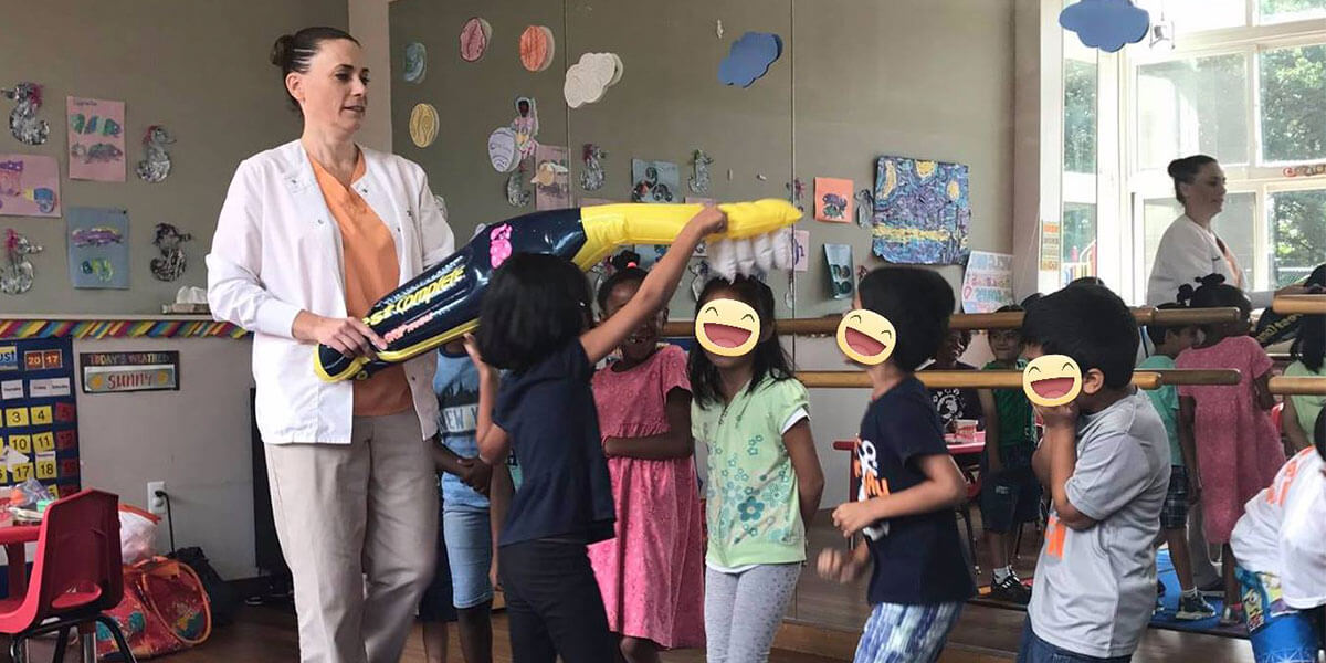 a group of children in a classroom playing with an inflatable tooth brush