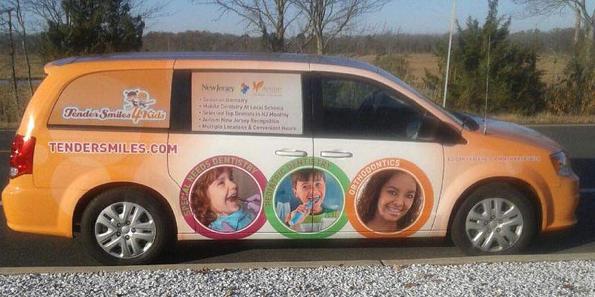 minivan wrapped in orange with Tender Smiles 4 Kids logo and dental information