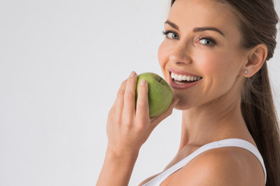smiling woman biting apple