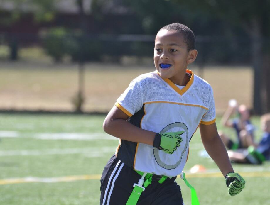 Young Child Playing Football Wearing Mouthguard