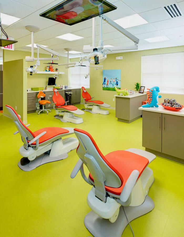 green dental examination room with orange and white chairs with toy dinosaurs on counter