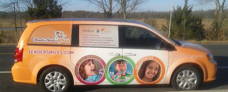 minivan wrapped in orange with Tender Smiles 4 Kids logo and dental information