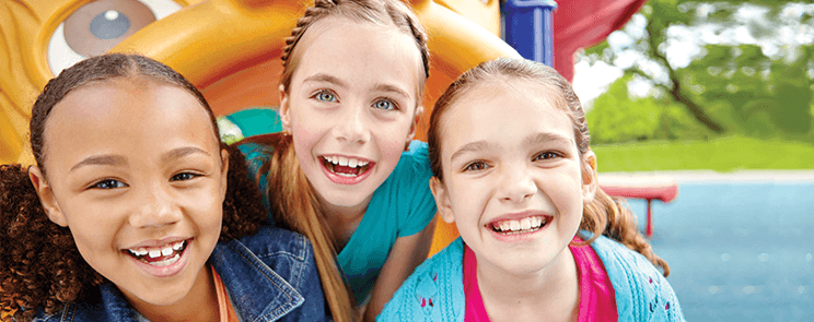 three smiling adolescent girls on a playground