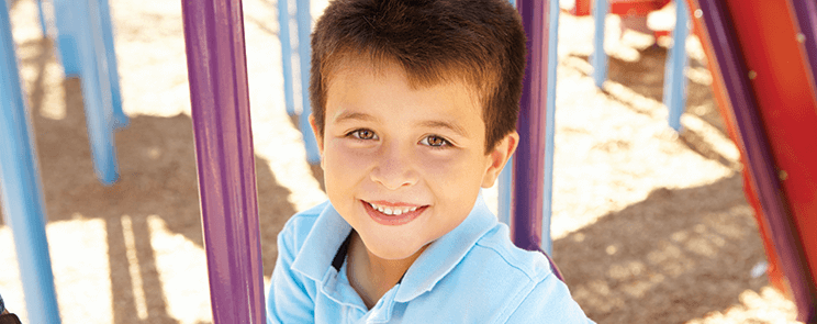 young boy in blue polo shirt smiling on a playground